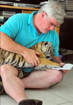 Hands-on research: Thomas French with a tiger cub at the home of the vet who worked with the Sumatran tiger featured in Zoo Story.