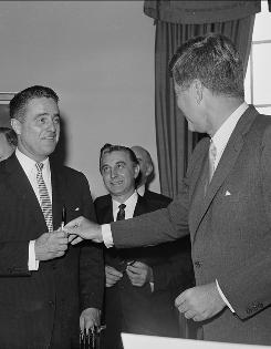 """In 1961, President John F. Kennedy hands a pen to brother-in-law Sargent Shriver after signing legislation at the White House giving the Peace Corps permanent status. Kennedy joshingly praised Shriver, head of the Corps, as """"one of the most effective lobbyists Washington has seen."""" Rep. Roman Pucinski, D-Ill., is at center."""