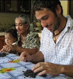 Peace Corps volunteer Mick Wigal, 29, of Youngstown, Ohio, sorts beans with his host family in Cano Negro, Costa Rica. Volunteers live in the communities they serve and work on a shoestring budget.