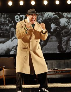 Calling the shots: Dan Lauria as football coach Vince Lombardi in front of a screen showing footage of his team, the Green Bay Packers.