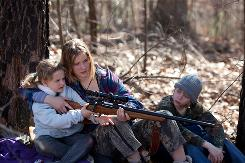Ree Dolly (Jennifer Lawrence) shows her younger siblings (played by Ashlee Thompson and Isaiah Stone) how to use a rifle in Winter's Bone.