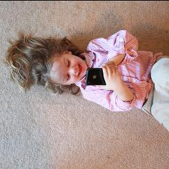 "Touch and play: Charlotte Stapleton, 3, plays with an iPhone at her home in Arlington, Va. ""She's always been drawn to it,"" says her mom, Ainsley."