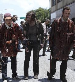 Steven Yeun, left, and Andrew Lincoln, right, try to blend in with the zombie population iin The Walking Dead.