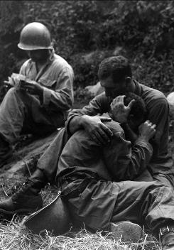 The wages of warfare: A corpsman, left, fills out casualty tags as a soldier consoles another soldier after the loss of a comrade in the Korean War.
