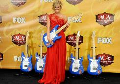 Recording artist Carrie Underwood poses with guitar trophies she won at the American Country Awards at the MGM Grand Garden Arena December 6, 2010 in Las Vegas.