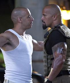 The bald and the boisterous: Vin Diesel, left, and Dwayne Johnson face off in Fast Five, due in theaters April 29.