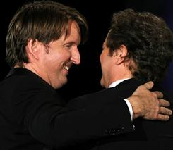 Director Tom Hooper (left) hugs actor Colin Firth, star of The King's Speech, after winning the best director award.
