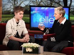 Justin Bieber gives Ellen DeGeneres a lock of his hair after cutting it for charity.