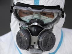 A worker wears protective clothing waits to scan people for radiation at an emergency center Sunday in Koriyama, Japan.