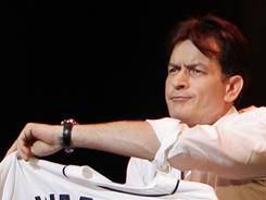 Working the crowd: Charlie Sheen shows off his Detroit Tigers jersey Saturday night. 