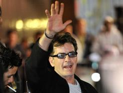 Charlie Sheen waves to fans as he leaves the Chicago Theatre during his month-long, 20-city variety show tour.