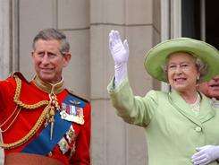 Britain's Queen Elizabeth II and her son Prince Charles wave to onlookers from Buckingham Palace.