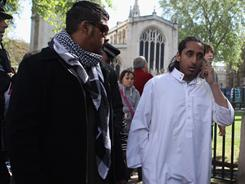 Assad Ullah and other members of Muslims Against Crusades walk past Westminster Abbey with police officers on their way to a meeting at Scotland Yard in London. With only two days to go before the wedding, security checks and last -minute preparations are continuing around Westminster Abbey, Buckingham Palace and along the route that Prince William and Catherine Middleton will take.