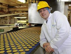 Rich Tea biscuits, fresh from the oven, move on a conveyor belt next to McVitie's factory general manager Andy Brammer.