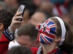 A royal wedding spectator holds up her phone outside Westminster Abbey, as so many did to take pictures, update Facebook or tweet.