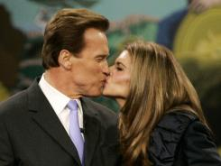 Arnold Schwarzenegger kisses his wife, Maria Shriver, after taking his oath of office as California governor in 2007.