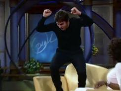 "Tom Cruise expresses his love for Katie Holmes during a 2005 taping of the  Oprah Winfrey show. ""Jump the couch"" (to exhibit strange or frenetic behavior) enters the lexicon."