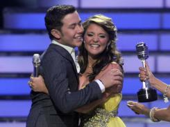 Winner: Scotty McCreery hugs Lauren Alaina, accepts the trophy from Jennifer Lopez.