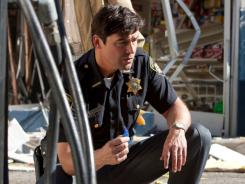 A crash, an explosion:   Kyle Chandler seeks clues to strange goings-on.