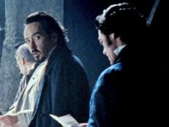 E.A. Poe (John Cusack, left,) and Inspector Emmett Fields (right) question some itinerant stagehands backstage after a gruesome murder.