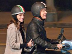 Odd couple: Julia Roberts and Tom Hank join the moped crowd in 'Larry Crowne.'