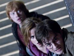 Wands at the ready: Rupert Grint, left,  Emma Watson and Daniel Radcliffe battled evil for the good of their school, Hogwarts.