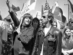 this April 2, 1973 file photo, actress Jane Fonda holds her arm up in the air as she joins a group of anti-war demonstrators on a march toward the  White House to protest the visit of South Vietnam's President Nguyen Van Thieu in San Clemente, Calif.