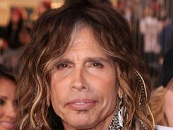 Musician Steven Tyler shakes a tailfeather. Actually, he shakes several in his long locks.