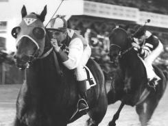 Seabiscuit and jockey George Woolf lead War Admiral and jockey Charles Kurtsinger in the first turn at  Pimlico in Baltimore on Nov. 1, 1938.  Seabiscuit won and set a  track record.