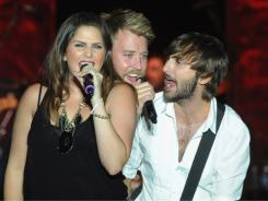 Hillary Scott, left, Charles Kelly and Dave Haywood perform at Country Thunder music festival in July.