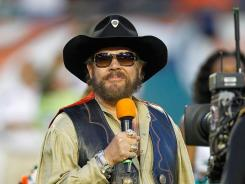 Country singer Hank Williams, Jr. greets the crowd during a game between the Miami Dolphins and the New England Patriots in Miami.