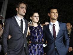 Actors Robert Pattinson, left, Kristen Stewart and Taylor Lautner arrive at the world premiere of 'The Twilight Saga: Breaking Dawn - Part 1'.