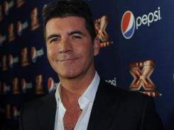 Simon Cowell, photographed at a viewing party for 'The X Factor,' cast the vote that caused a deadlock, so America's votes broke the tie.