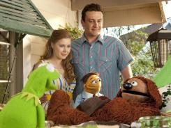 Kermit the Frog, Walter, Gary (Jason Segel) and Mary (Amy Adams) try to talk Rowlf the Dog into returning to show biz so they can save the Muppet Theater.