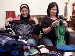 Samira Amen, left, gives some clothes and jewelry to her sister Shadia after making the decision to wear a hijab.