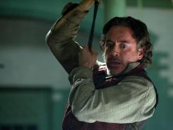 Sherlock Holmes, action hero:  Robert Downey Jr. swings into action against the nefarious Moriarty.