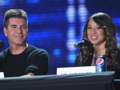 Melanie Amaro, the youngest and only female act left in the competition, was originally eliminated by Simon Cowell, but he went to her home and begged for her return.