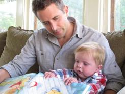 Matt Hammitt reads a book to his 1-year-old son, Bowen, on Sept. 14 at their home in Perrysburg, Ohio.