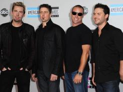 Chad Kroeger, Daniel Adair, Mike Kroeger and Ryan Peake of Nickelback, who presented at Sunday's American Music Awards, launched their new album with two singles.