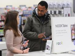 Sales season:  Lisa Gross answers questions about the Nook for customer Asfaha Beyene at Barnes and Noble in Tysons Corner Center in McLean, Va.