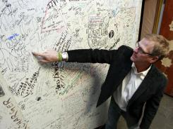 Jeff Nicholas, Surf Ballroom & Museum president, points out the signature of Maria Elena Holly, widow of Buddy Holly, among the many autographs inside the Surf Ballroom's green room.