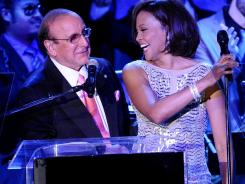 Host Clive Davis onstage with Whitney Houston at his 2011 Pre-Grammy Gala.