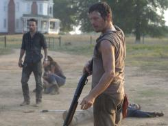 Reedus' cranky redneck character, Daryl Dixon (center), is all business when it comes to staying alive.