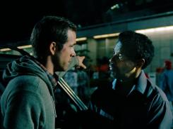 """Dynamic duo: The strong performances and terrific chemistry between Ryan Reynolds, left, and Denzel Washington power """"Safe House."""""""