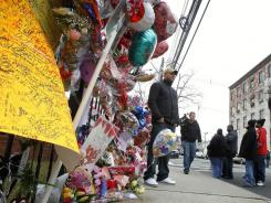 A man poses for a photo in front of a make-shift memorial as fans pay their respects to Whitney Houston at New Hope Baptist Church, in Newark, N.J., on Wednesday.