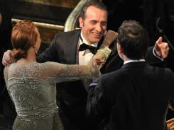 Best actor winner Jean Dujardin is congratulated by his 'Artist' co-star, Berenice Bejo, and director Michel Hazanavicius.