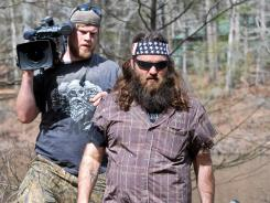 "'Duck Dynasty': ""It's a state of mind,"" says Willie Robertson of West Monroe, L.A., trailed by cameraman Ethan Edwards and on the lookout for a snake."