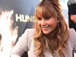 Star sighting: Jennifer Lawrence visits fans outside Nokia Theatre on Sunday, signing autographs and posing for photos the day before the 'Hunger Games' premiere.