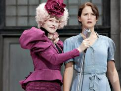 Effie Trinket (Elizabeth Banks) introduces protagonist Katniss Everdeen (Jennifer Lawrence) at the start of the Hunger Games.