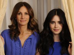 Fairest of them all: Julia Roberts plays the Evil Queen to Lily Collins' Snow White in 'Mirror Mirror,' out Friday. The two pull back the curtain at the Hotel Amarano in Burbank, Calif.